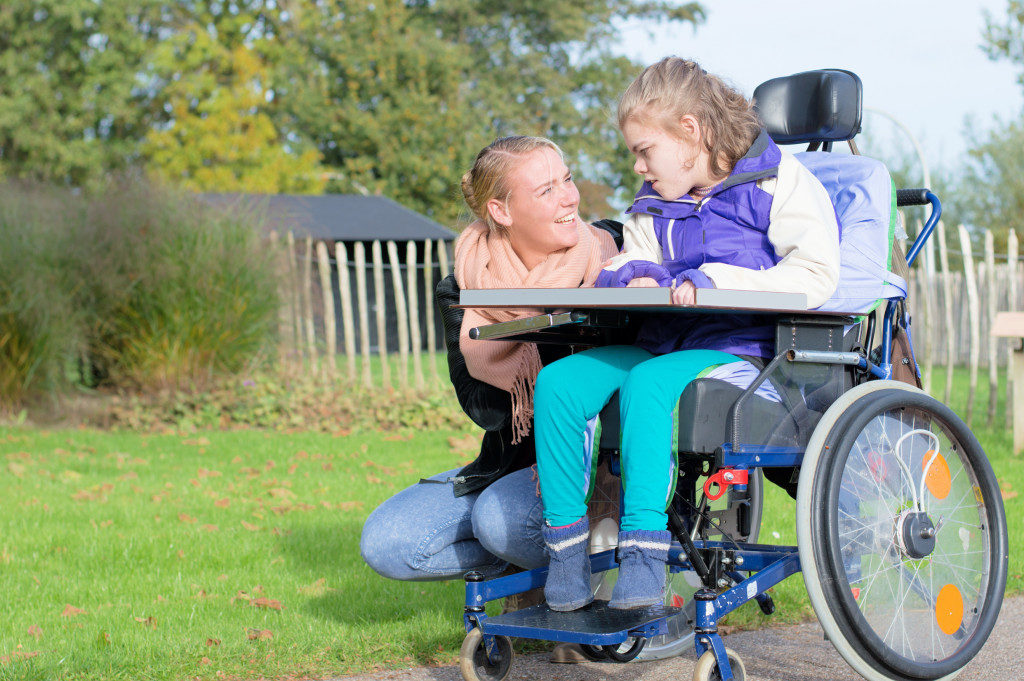 Mother and her daughter who is sitting on the wheelchair